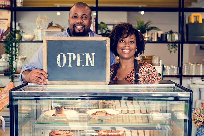 retail-couple-holding-open-sign